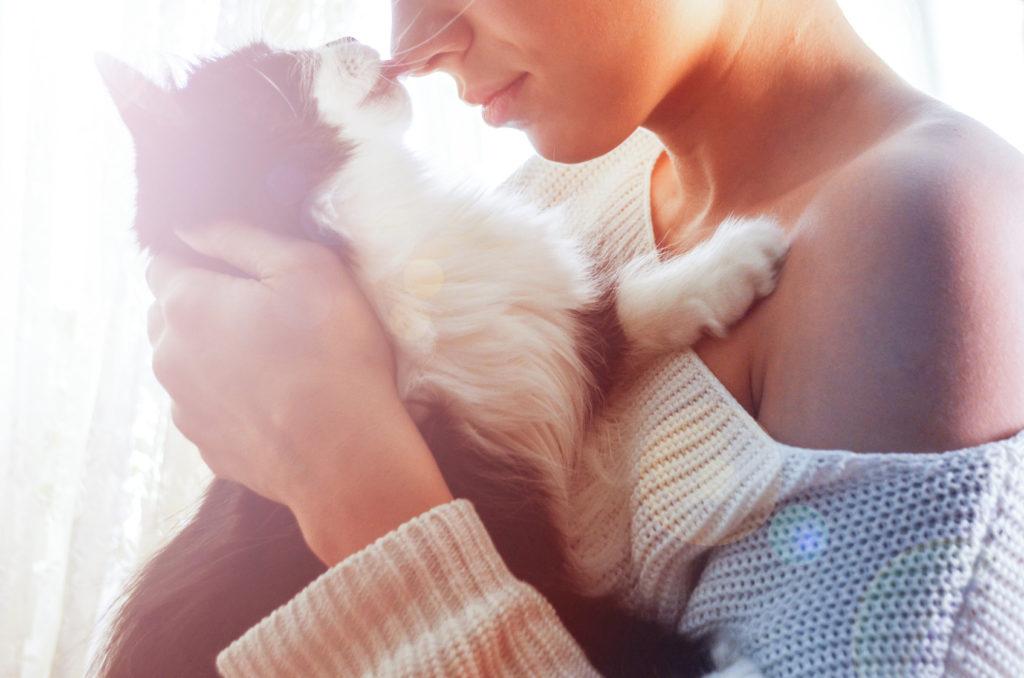 Femme qui porte un chatm son nez est collé à la truffe du chat