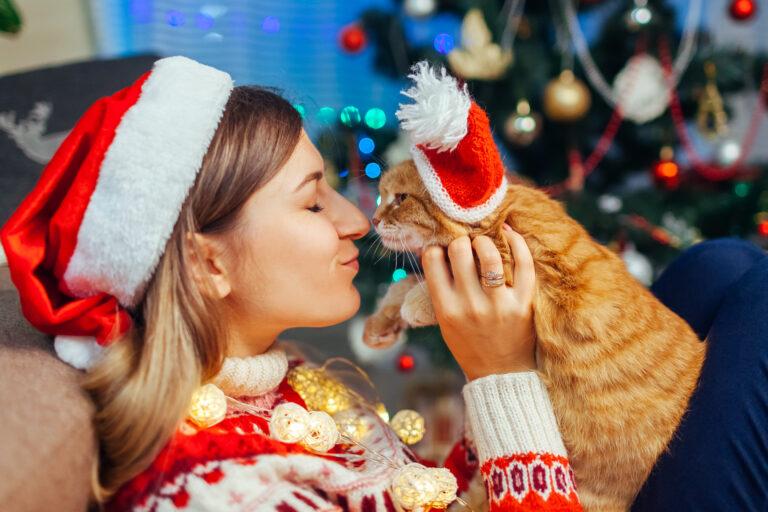 Une femme et son chat célèbrent Noël ensemble.